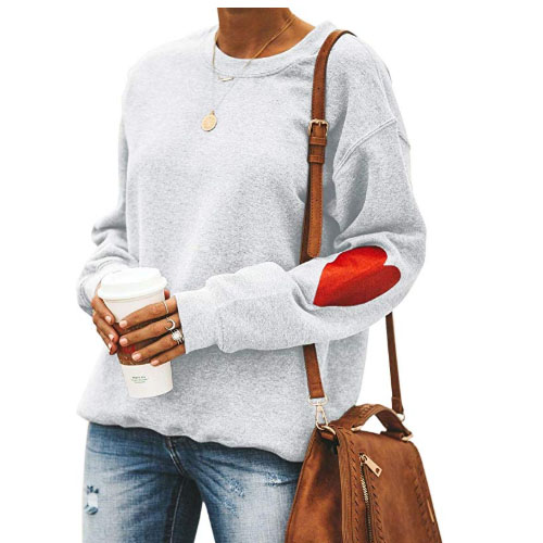 white woman sweater with red heart symbol on elbows